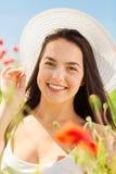 La mujer joven sonriente en sombrero de paja en amapola coloca Imágenes de archivo libres de regalías