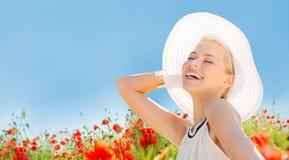 La mujer joven sonriente en sombrero de paja en amapola coloca Imagenes de archivo