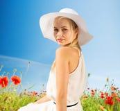 La mujer joven sonriente en sombrero de paja en amapola coloca Imagen de archivo libre de regalías
