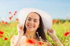 La mujer joven sonriente en sombrero de paja en amapola coloca Foto de archivo libre de regalías