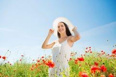 La mujer joven sonriente en sombrero de paja en amapola coloca Fotografía de archivo