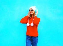 La mujer joven sonriente en suéter rojo, escucha la música en auriculares inalámbricos Foto de archivo libre de regalías