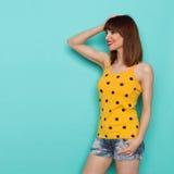 La mujer joven sonriente en top sin mangas punteado amarillo está mirando lejos Imagen de archivo libre de regalías