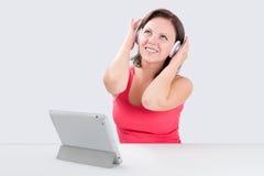 La mujer joven sonriente está escuchando la música Fotos de archivo