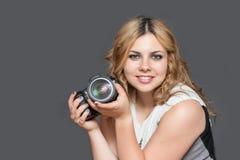 La mujer joven sonriente está sosteniendo una cámara en ambas manos Imagen de archivo