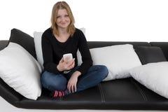 La mujer joven sonriente está utilizando su teléfono elegante aislado Imagenes de archivo