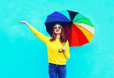 La mujer joven sonriente feliz con el paraguas colorido en el día del otoño que miraba para arriba sobre amarillo que llevaba del Imágenes de archivo libres de regalías