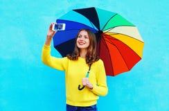 La mujer joven sonriente feliz con el paraguas colorido que toma la foto del otoño hace el autorretrato en smartphone sobre azul  Imagen de archivo libre de regalías