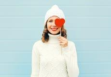 La mujer joven sonriente feliz con los labios rojos lleva a cabo el corazón de la piruleta que lleva el suéter hecho punto del so Fotos de archivo