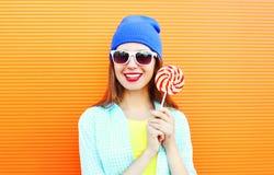 La mujer joven sonriente feliz del retrato de la moda es controles a la piruleta del palillo sobre naranja colorida Imagen de archivo libre de regalías