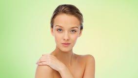 La mujer joven sonriente hace frente y los hombros sobre verde Imágenes de archivo libres de regalías