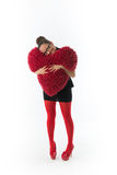 La mujer joven sonriente lleva a cabo un corazón rojo Fotografía de archivo libre de regalías