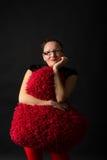 La mujer joven sonriente lleva a cabo un corazón rojo Imágenes de archivo libres de regalías
