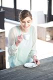 La mujer joven sonriente que goza de una taza de café aventaja Fotografía de archivo libre de regalías