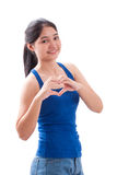 La mujer joven sonriente que hace el corazón forma con sus manos Fotografía de archivo libre de regalías