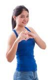 La mujer joven sonriente que hace el corazón forma con sus manos Fotos de archivo
