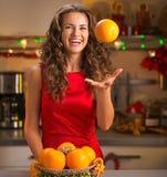 La mujer joven sonriente que lanzaba para arriba la naranja en la Navidad adornó ki Foto de archivo libre de regalías