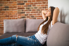 La mujer joven sonriente que mentía en el sofá en las manos por encima cerró ojos Imagen de archivo libre de regalías