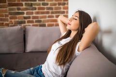 La mujer joven sonriente que mentía en el sofá en las manos por encima cerró ojos Foto de archivo