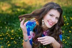 La mujer joven sonriente que miente en la hierba en el verano parquea Fotografía de archivo libre de regalías