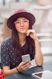 La mujer joven sonriente que mira el teléfono elegante en café hace compras imagenes de archivo