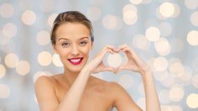 La mujer joven sonriente que muestra el corazón forma la muestra de la mano Imágenes de archivo libres de regalías