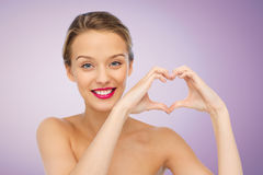 La mujer joven sonriente que muestra el corazón forma la muestra de la mano Fotos de archivo libres de regalías