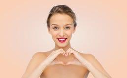 La mujer joven sonriente que muestra el corazón forma la muestra de la mano Imagen de archivo