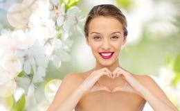 La mujer joven sonriente que muestra el corazón forma la muestra de la mano Fotos de archivo