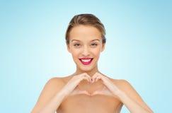 La mujer joven sonriente que muestra el corazón forma la muestra de la mano Fotografía de archivo libre de regalías