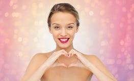 La mujer joven sonriente que muestra el corazón forma la muestra de la mano Imagenes de archivo