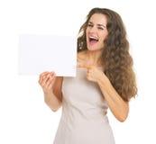 La mujer joven sonriente que señala en el papel en blanco cubre Fotografía de archivo libre de regalías