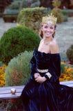 La mujer joven sonriente se vistió como la reina que sostenía una manzana Imagen de archivo