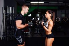 La mujer joven sonriente y el instructor personal ejercitan en gimnasio Imagen de archivo