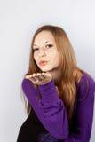 La mujer joven sopla en una mano (da un beso del aire) Fotos de archivo
