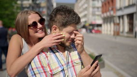 La mujer joven sorprende al hombre que espera cubriendo sus ojos almacen de video