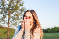 La mujer joven sorprendida con entrega su boca al aire libre Imagen de archivo