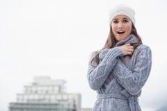 La mujer joven sorprendida con invierno viste en la presentación Fotos de archivo