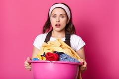 La mujer joven sostiene el lavabo por completo del lino limpio, ama de casa parece cansada después de hacer el lavadero, trabajos foto de archivo
