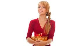 La mujer joven sostiene el rectángulo de regalo del oro como corazón Imagen de archivo libre de regalías