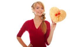 La mujer joven sostiene el rectángulo de regalo disponible del oro como corazón Foto de archivo libre de regalías