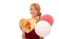 La mujer joven sostiene el rectángulo y los globos de regalo del oro Imagenes de archivo