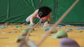 La mujer joven sube en la pared de la roca en club de deportes almacen de metraje de vídeo