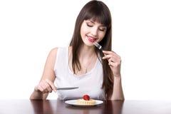 La mujer joven tentó a comer la torta Imagen de archivo