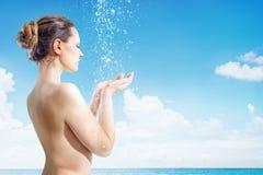 La mujer joven tiene ducha en la playa tropical fotos de archivo