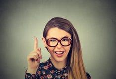 La mujer joven tiene idea, señalando con el finger para arriba Fotos de archivo