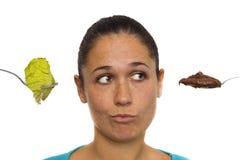 La mujer joven tiene que eligió entre sano o sabroso Imagenes de archivo