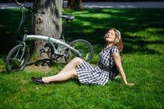 La mujer joven tiene resto cerca de la bicicleta en el parque Fotografía de archivo
