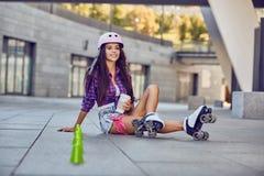 La mujer joven tiene un resto después de rollerblading y de beber el café Fotos de archivo