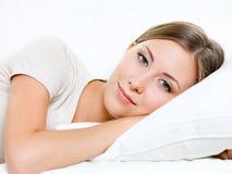 La mujer joven tiene un resto en la cama imagen de archivo